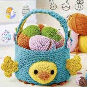 Связанная крючком пасхальная корзинка в виде утки, наполненная рукодельными яйцамика и яйца